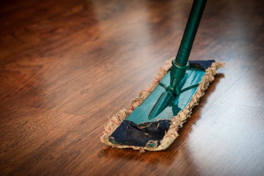 image: Person mopping wooden floor