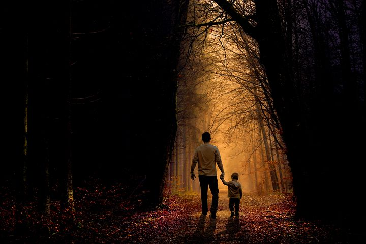image: father and son holding hands walking through forest