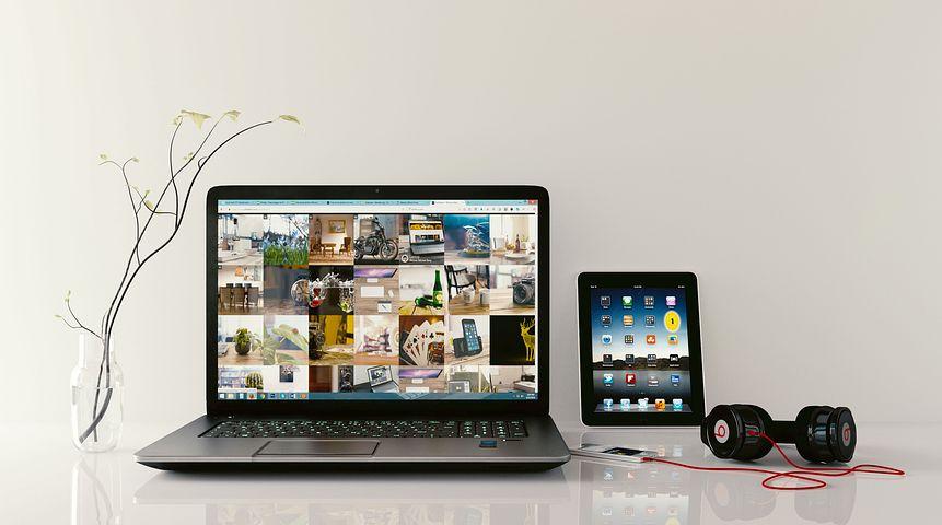 image: laptop tablet headphones on table