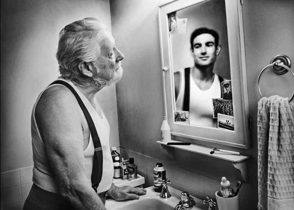 Image: Old man looking into mirror, reflection is a young man