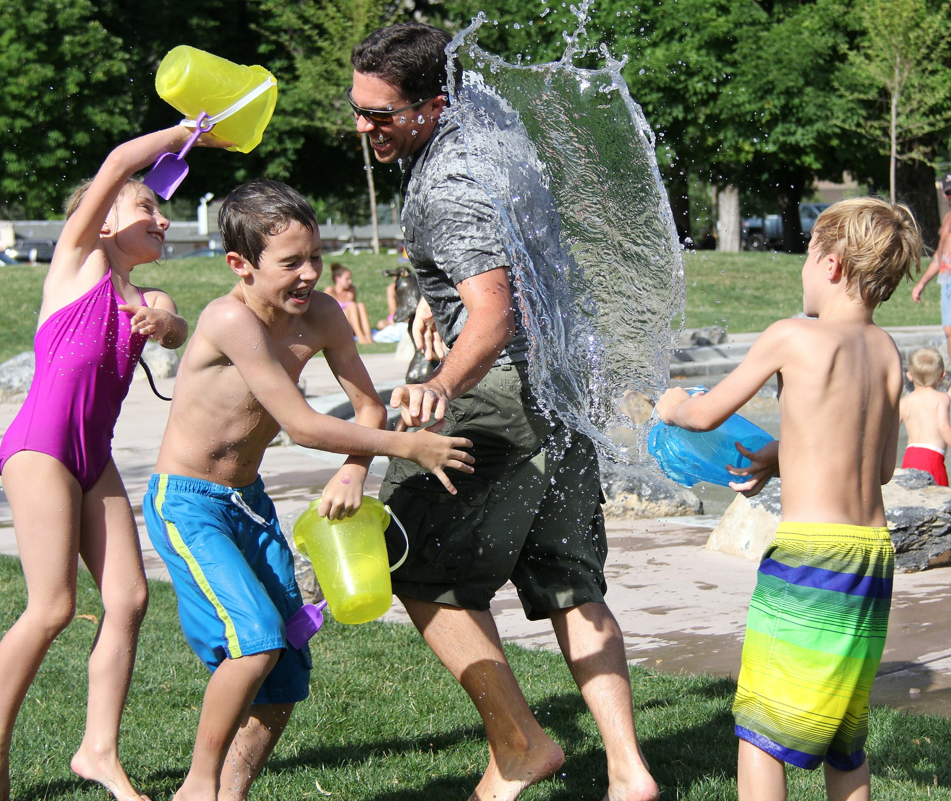 Image: Man and children laughing having a water fight