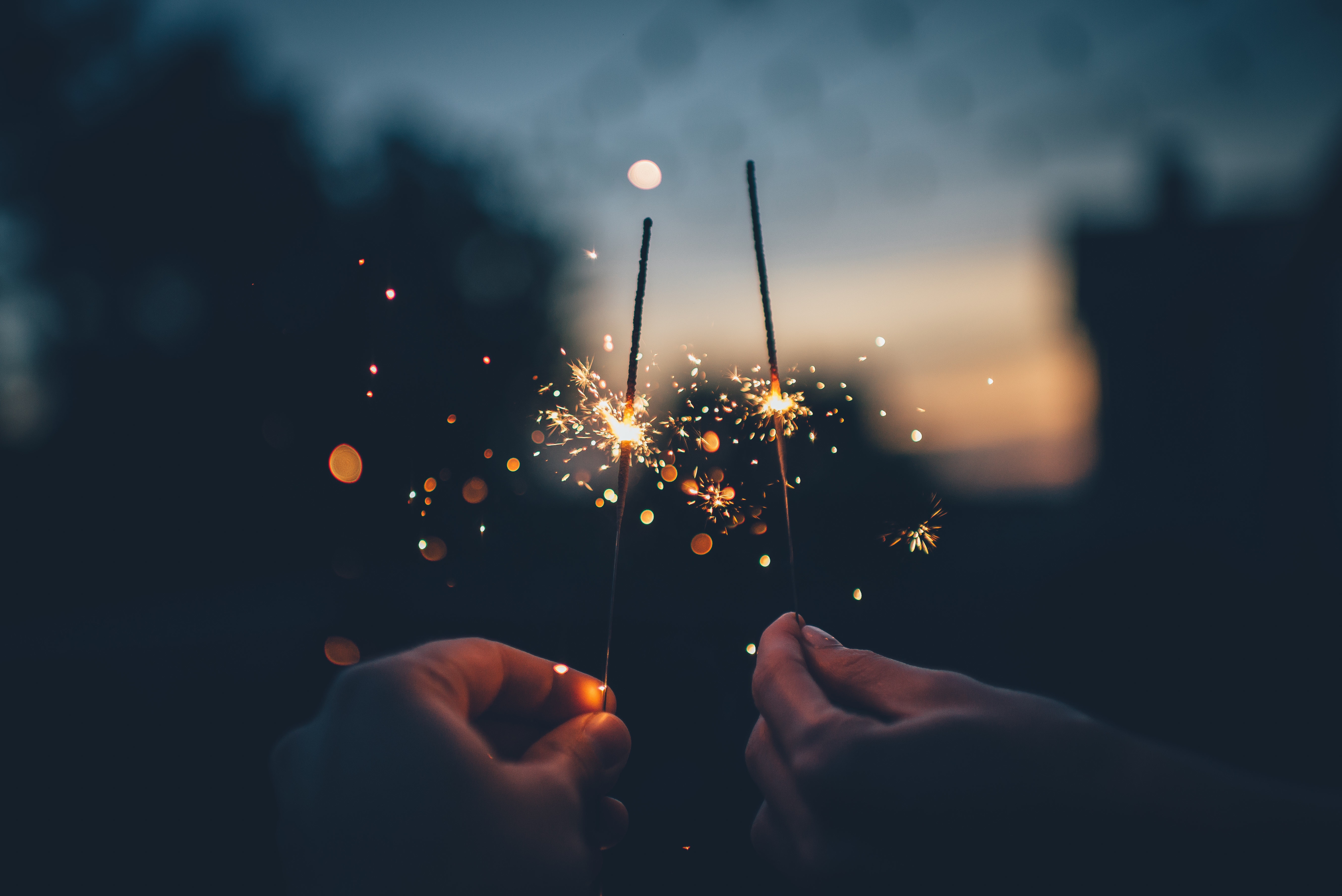 Image: two hands holding fire sparklers
